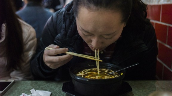 A woman eats noodles in a restaurant in Beijing in this file photo from November 2014.