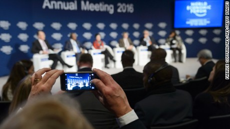 A participant takes a picture with his mobile phone during a session of the World Economic Forum (WEF) annual meeting in Davos on January 22, 2016.
