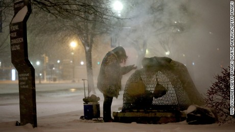 WASHINGTON, DC - JANUARY 22: A homeless woman tires to keep warm near a steam grate on Constitution Avenue January 22, 2016 in Washington, DC. A major snowstorm is forecasted for the East Coast this weekend with some areas expected to receive up to 30 inches of snow . (Photo by Win McNamee/Getty Images)