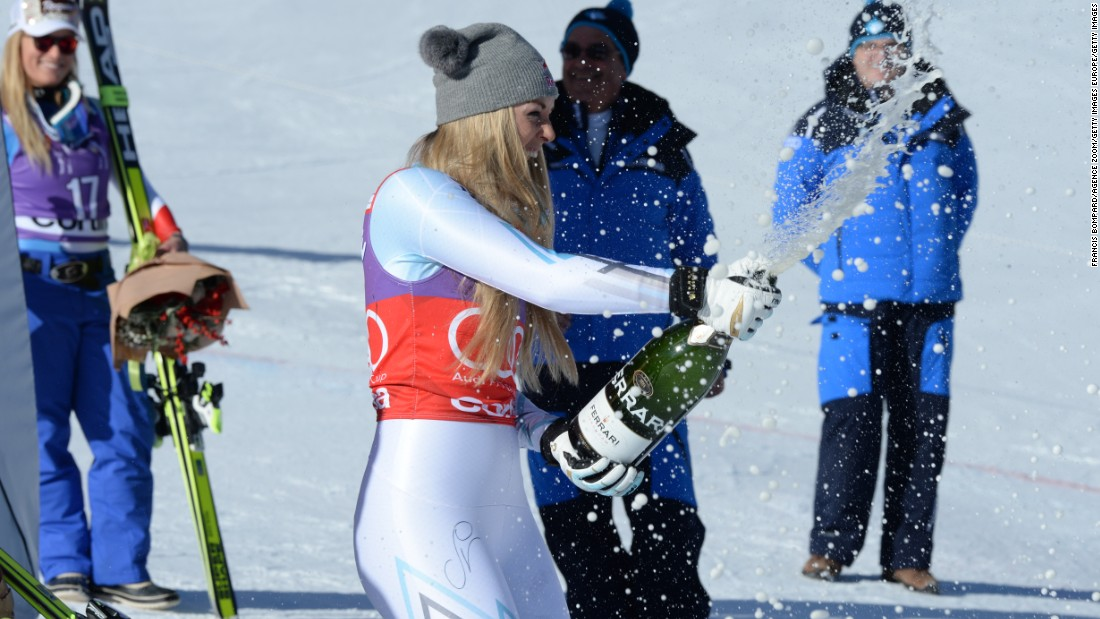 A delighted Vonn celebrates by spraying champagne over her bystanders.