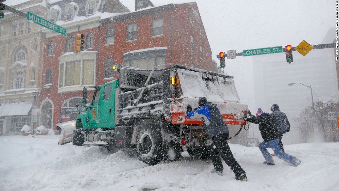 Chris Holder, left, and Chris Hauger try to push a loaded six-wheel salt truck in Baltimore on January 23.