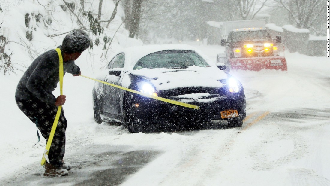 Michael McDonald attempts to pull his friend's car out of snow in Irvington, New York, on January 23. As his friend steered and gently accelerated, McDonald was able to get the car out of the snow and up the hill.