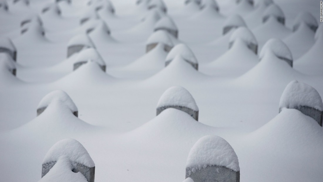 Headstones jut from the snow at Arlington National Cemetery.