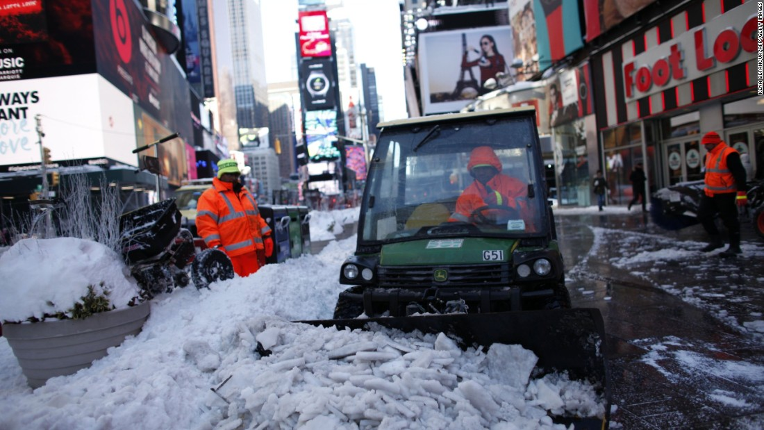 Workers clean a snow-covered street in New York's Times Square on January 24.