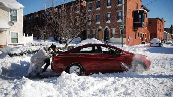 A family tries to push out a snow-bound car in Philadelphia on January 24.