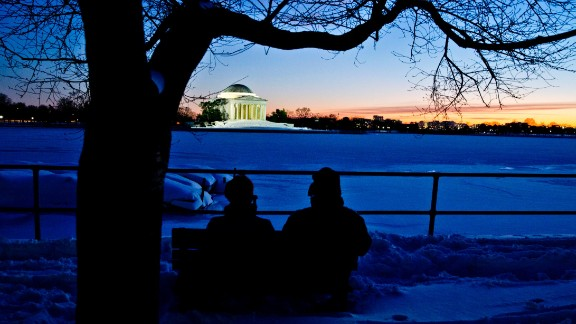 Pirjo Garby, left, and Tom Henry, both of Washington, sit near the Tidal Basin and watch the sunset behind the Jefferson Memorial on Sunday, January 24.