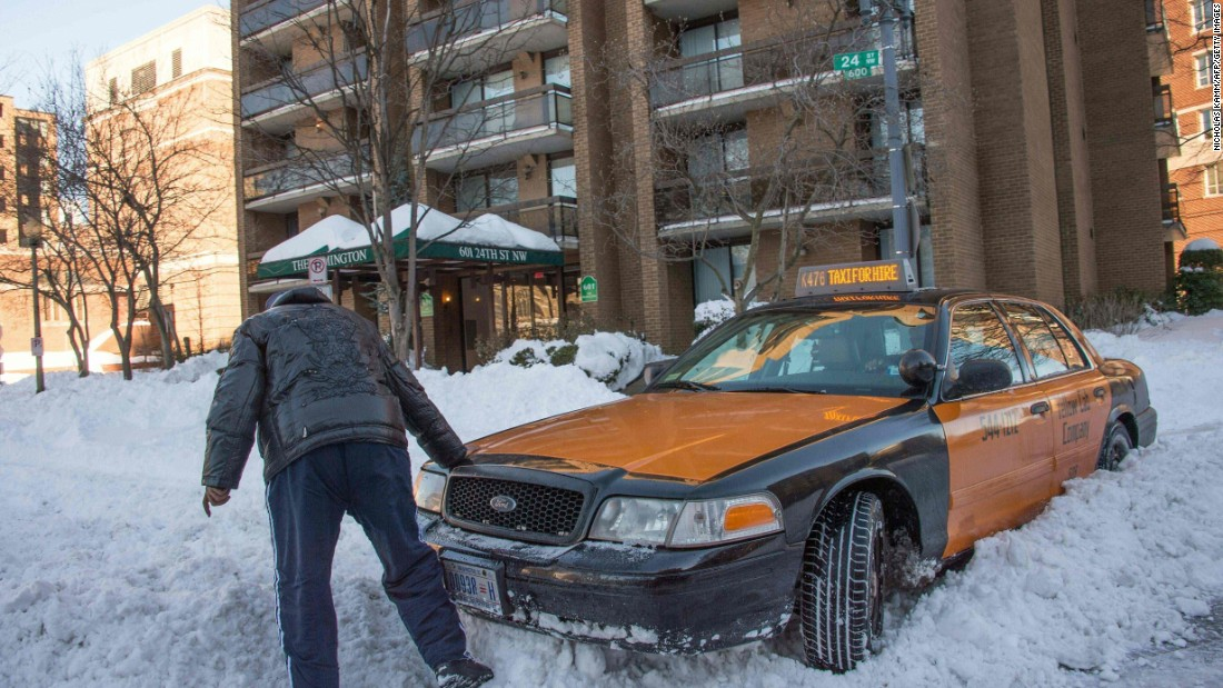 A taxi driver in Washington tries to get his car out of the snow on January 24.