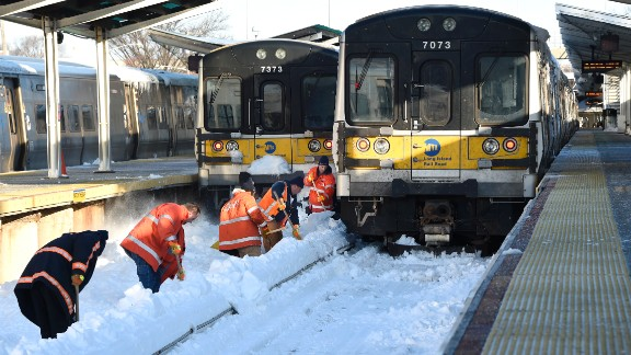 Long Island Railroad workers clear snow off train tracks in Port Washington, New York, on Monday, January 25. A massive winter storm clobbered the East Coast this weekend, shutting down travel in many of the nation's largest cities.
