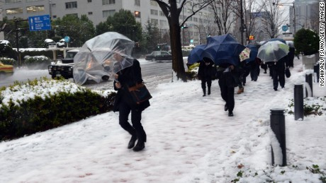 Commuters walk on a snow covered road in Tokyo on January 18, 2016. Heavy snow blanketed Tokyo metropolitan area and transportation systems were paralyzed.