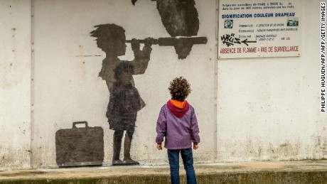 A child looks at a Banksy mural representing migrant children, in Calais in December 2015.