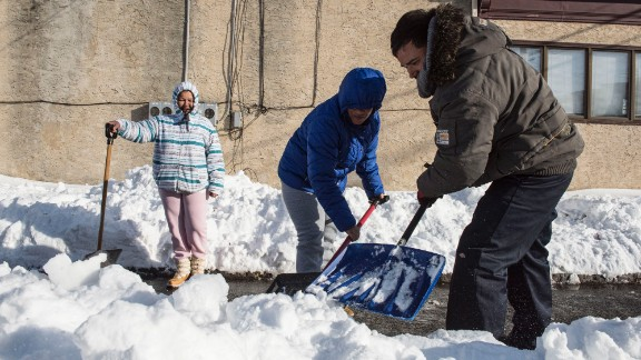 People shovel snow from a covered street in Wilmington, Delaware, on January 25.