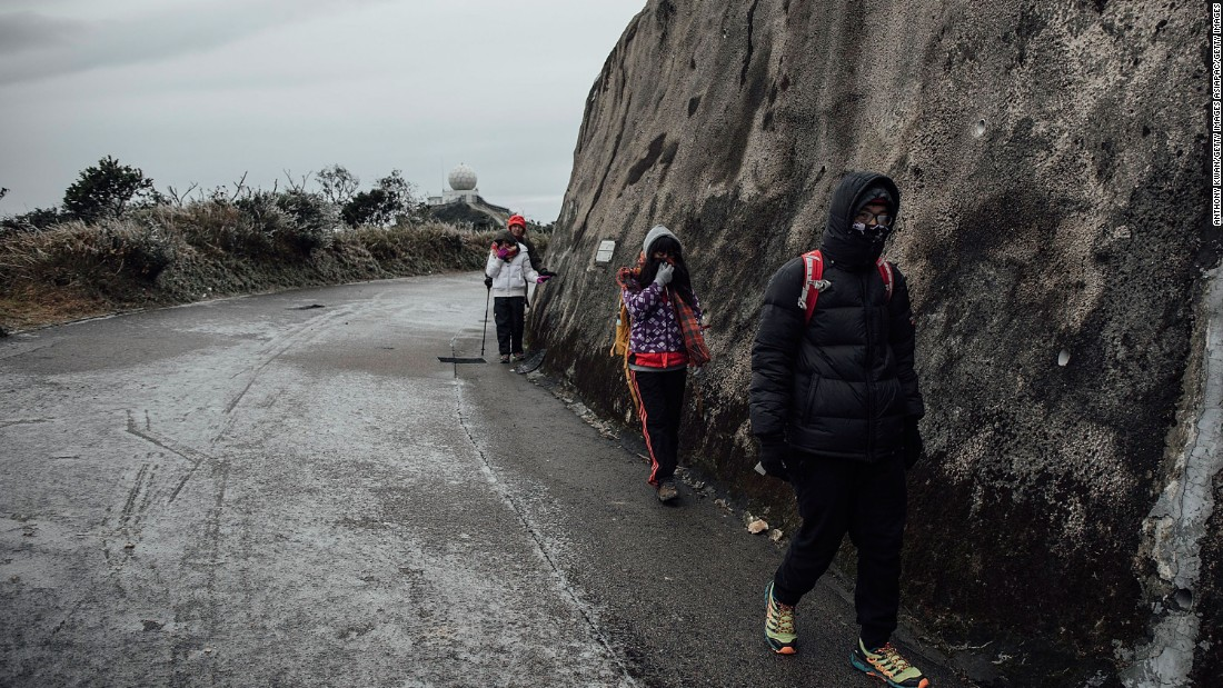 Hikers walk on icy road in sub-zero temperature on Tai Mo Shan, Hong Kong's highest peak on January 24. Many looking for sights of snow and frost in the subtropic city were trapped on the city's highest mountains as a result of iced-over roads and extreme cold.