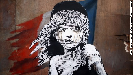 LONDON, ENGLAND - JANUARY 25:  A Banksy artwork is created opposite the French embassy on January 25, 2016 in London, England. The graffiti, which depicts a young girl from the musical Les Miserables with tears in her eyes as CS gas moves towards her, criticises the use of teargas in the 'Jungle' migrant camp in Calais.  (Photo by Carl Court/Getty Images)