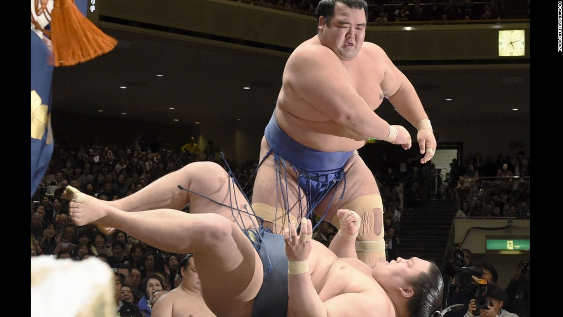 Ozeki Kotoshogiku throws Goeido on Sunday, January 24, to win the New Year Grand Sumo Tournament in Tokyo. He is the first Japanese wrestler to win an Emperor's Cup since 2006.