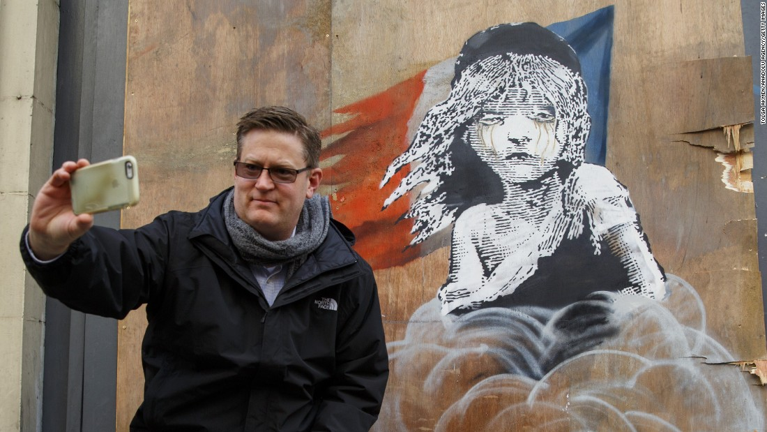 "A man takes a selfie with the new Banksy mural opposite the French Embassy in London on Monday, January 25. The image, which recreates a poster from the French musical ""Les Misérables,"" <a href=""http://www.cnn.com/2016/01/25/arts/banksy-new-art-french-embassy/"" target=""_blank"">shows a crying young girl enveloped by tear gas.</a> The artwork is criticizing authorities' alleged use of tear gas at a refugee camp in Calais, France."