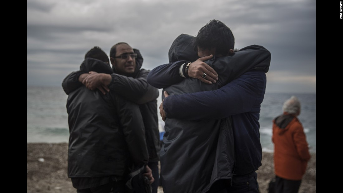 Men hug each other on the beach shortly after crossing the Aegean Sea on Sunday, January 10.