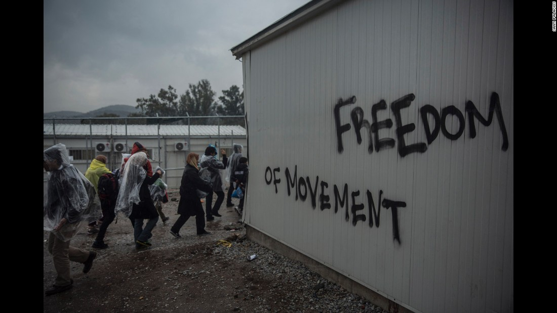 Refugees walk on January 10 in front of graffiti outside a registering center in the village of Moria on Lesbos.