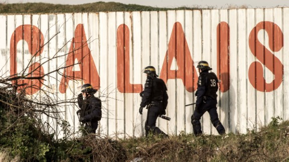 French riot police walk in front of a fence near the A16 motorway near Calais, France.