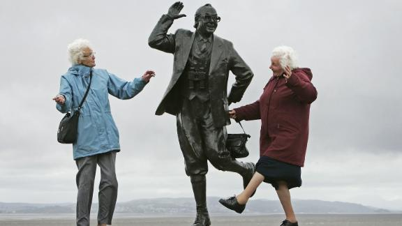 MORCAMBE, UNITED KINGDOM - JUNE 22: Despite inclement weather pensioners raise a happy smile as they perform the famously British dance of comedians Morcambe and Wise next to a statue of Eric Morcambe, at Morcambe Bayon  June 22, 2006, in Morcambe, England.  Confidence & Happiness specialist, Scientist Cliff Arnall from the University of Cardiff has identified June 23, 2006 as being the happiest day of the year. His calculations were based on outdoor activity, nature, social interaction, childhood summers, positive memories, temperature and holidays. (Photo by Christopher Furlong/Getty Images)