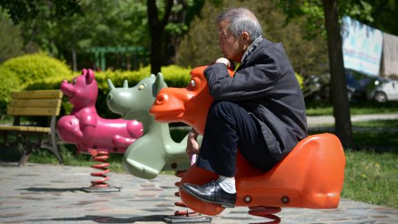 An elderly man sits on a hobby horse at a residential area in Beijing on May 4, 2015.      AFP PHOTO/ WANG ZHAO        (Photo credit should read WANG ZHAO/AFP/Getty Images)