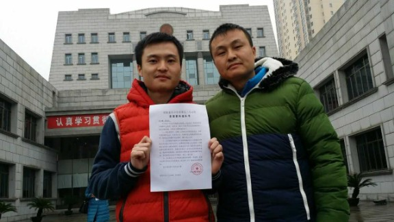 Sun Wenlin (left) and his partner Hu Mingliang stand in front of the Changsha Furong District People's Court on January 5, 2016, the day the court accepted their suit against the marriage registry.