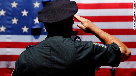 BOSTON, MA - JULY 5: A police officer salutes during the National Anthem before the first game of a doubleheader between the Baltimore Orioles and the Boston Red Sox at Fenway Park on July 5, 2014 in Boston, Massachusetts.  (Photo by Jim Rogash/Getty Images)