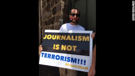 Phil Moore -- one of two Le Monde journalists recently arrested in Burundi --  holds a sign advocating for the release of Al Jazeera journalists held until recently in Egypt in this February 2014 picture.