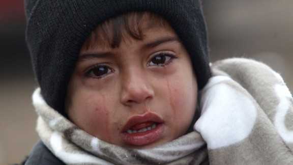 A young boy cries near the Miratovac refugee camp after arriving from Macedonia on a very cold winter morning.