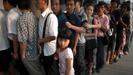 This picture taken in August 2011 shows a girl standing beside her father as hundreds of Chinese parents queue up to see a doctor outside a children's hospital in Beijing.