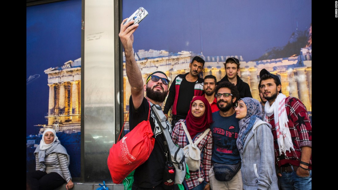 Somar and his sisters take a selfie with friends in front of an Acropolis photo in Athens, Greece.