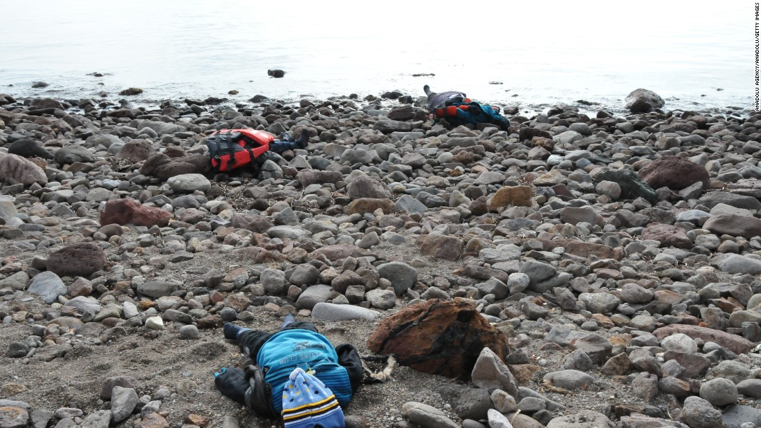 The bodies of migrants are seen on a beach after the boat capsized in the Aegean Sea. Authorities report that at least five children were among the dead.