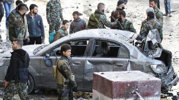 Syrian pro-government forces gather at the site of a deadly triple bombing Sunday, January 31, in the Damascus suburb of Sayeda Zeynab. ISIS claimed responsibility for the attack, according to a statement circulating online from supporters of the terrorist group.