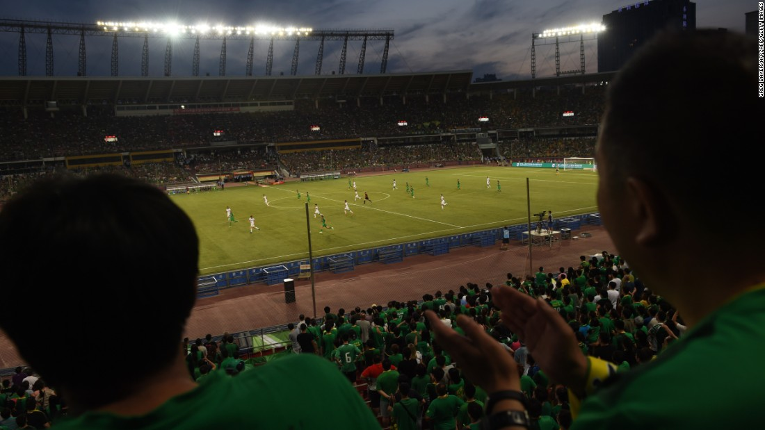 This photo taken on June 20, 2015 shows fans (foreground) wearing the colors of the Beijing Guoan team as they watch the team's Chinese Super League  match against Tianjin Teda in Beijing.