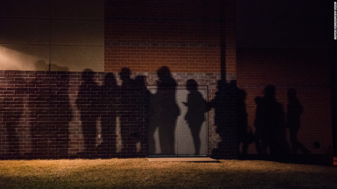 The shadows of lined-up caucusgoers are seen outside a school in West Des Moines.