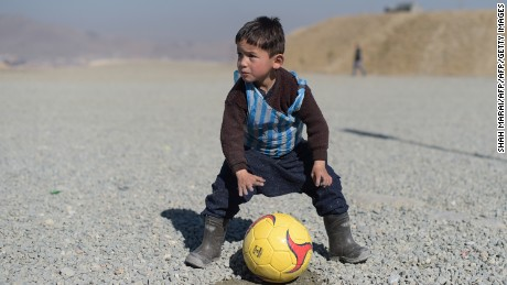 TOPSHOT - Afghan boy five-year-old Murtaza Ahmadi, a young Lionel Messi fan, plays football in Kabul on February 1, 2016. Barcelona star Lionel Messi is hoping to arrange a meeting with an Afghan boy who shot to fame after pictures of him dressed in a striped plastic bag jersey went viral, Kabul's football federation said on February 1. AFP PHOTO / SHAH Marai / AFP / SHAH MARAI        (Photo credit should read SHAH MARAI/AFP/Getty Images)
