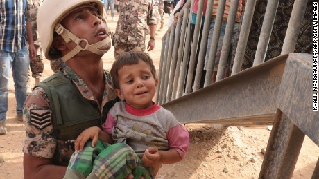 A Jordanian soldier carries a Syrian refugee at the al-Roqban makeshift camp, on the border with Syria, in September.