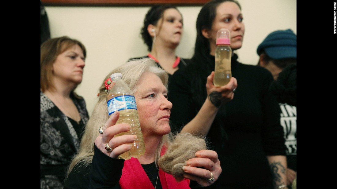 "Flint, Michigan, residents Gladyes Williamson, center, and Jessica Owens, right, attend the House Committee on Oversight and Government Reform hearing on Capitol Hill about the Flint <a href=""http://www.cnn.com/2016/02/03/us/flint-michigan-water-crisis/"" target=""_blank"">water crisis</a>. Williamson and Owens hold bottles of contaminated water, and Williamson shows a clump of her hair. The two traveled to Washington by bus with other families to demand that Gov. Rick Snyder be brought to testify before Congress. The House hearing was on Wednesday, February 3."