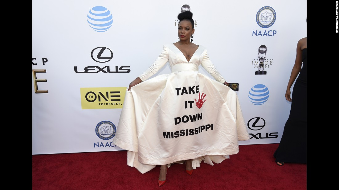 "Aunjanue Ellis arrives at the 47th NAACP Image Awards on Friday, February 5. The ""Quantico"" star wore a white dress emblazoned with the phrase ""Take It Down Mississippi,"" a reference to ongoing debate over the state flag, the last in the country to incorporate the Confederate battle emblem."