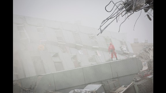 Heavy smoke comes out from a collapsed building as rescue personnel search for survivors in Tainan.