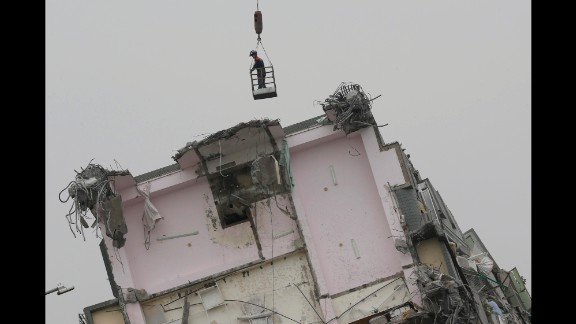 A rescue worker hangs from a crane while searching a collapsed building in Tainan.