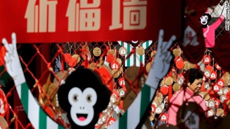 A woman walks past New Year's wish cards written by visitors on display at the Sanlitun Village shopping mall in Beijing, February 4.