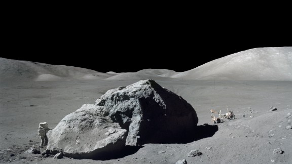 Harrison Schmitt stands next to a huge lunar boulder during an Apollo 17 moon walk.