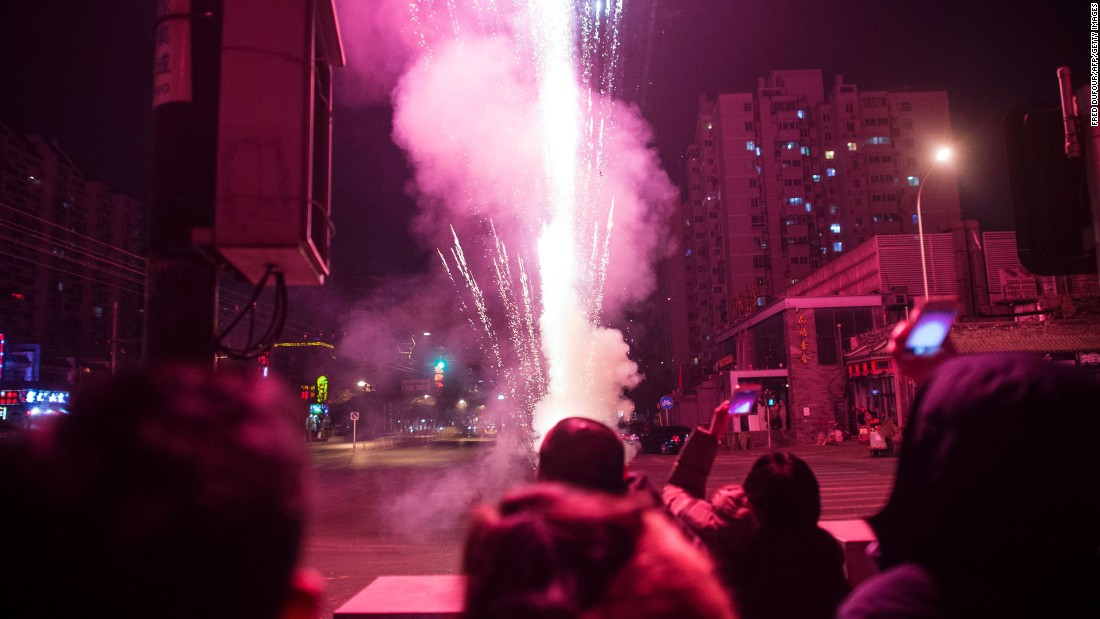 People watch fireworks on a street in Beijing on February 7.