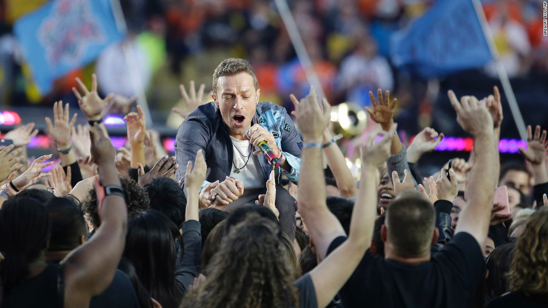 Coldplay frontman Chris Martin greets fans during his band's performance.