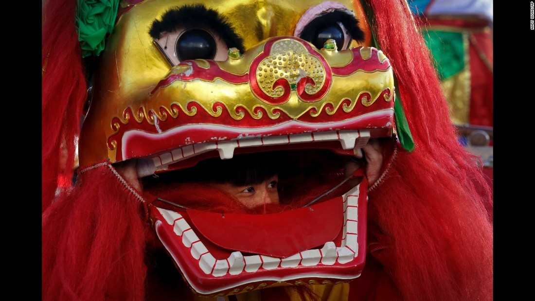A performer looks out from the mouth of a lion head at Ditan Park in Beijing on February 8.