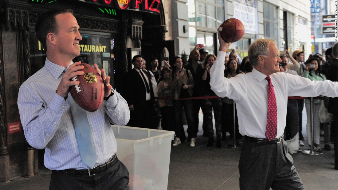 "Manning and talk-show host David Letterman throw footballs at New York City cabs during a ""Late Show"" taping in 2014."