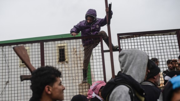 A child tries to climb over a fence near the Turkish border as Syrians fleeing the northern city of Aleppo wait on February 6.