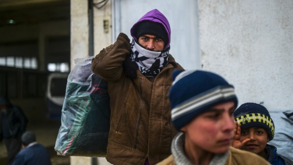 A refugee carries a heavy bag of items near the Turkish border gate on February 6.