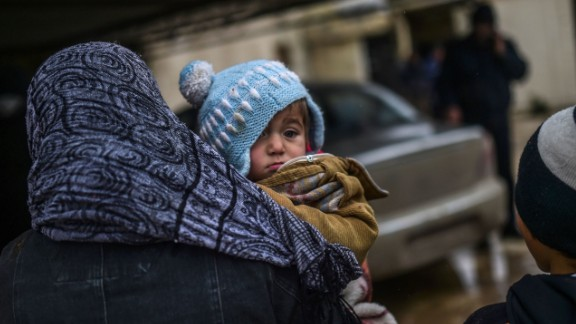 Syrian refugees await their fate near the Turkish border gate as they flee the northern embattled city of Aleppo on February 6, 2016.