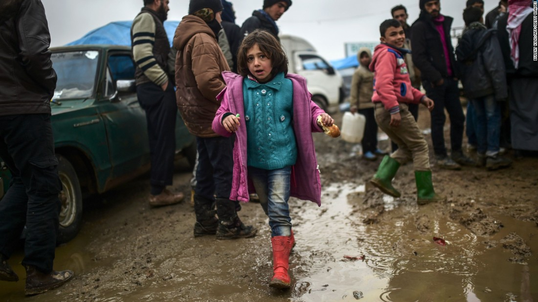 Refugees brave the cold and rain as they arrive at the Turkish border on February 6.
